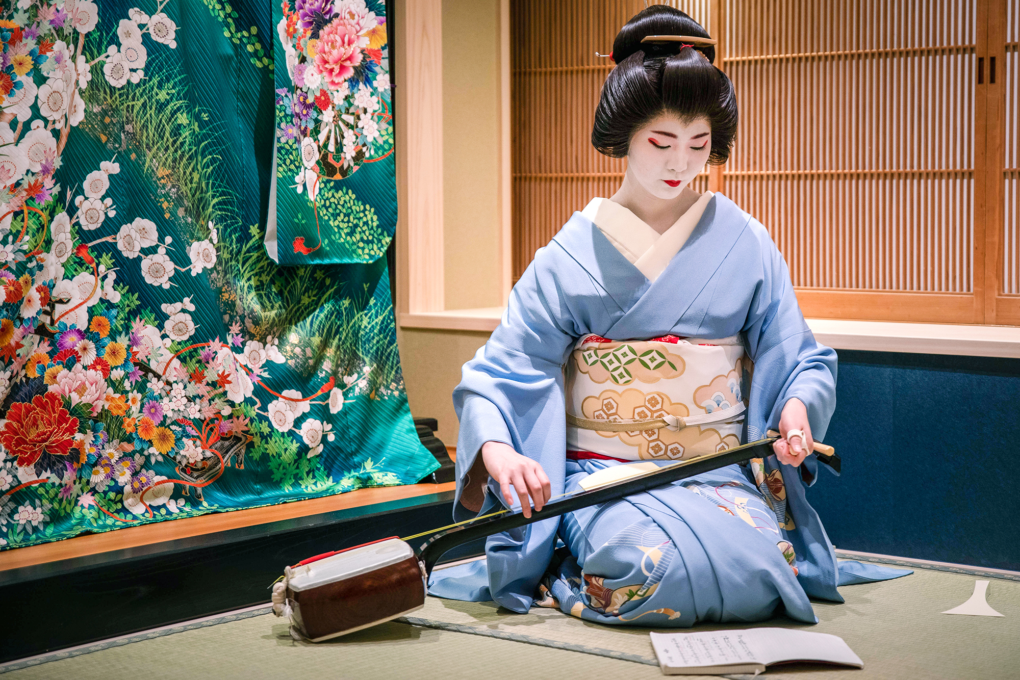 Young maiko tuning her shamishen before a performance.