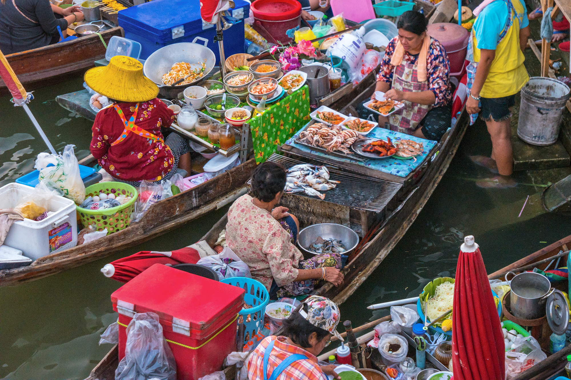 Local vendors selling fresh fruits and vegetables at Amphawa Floating Market.